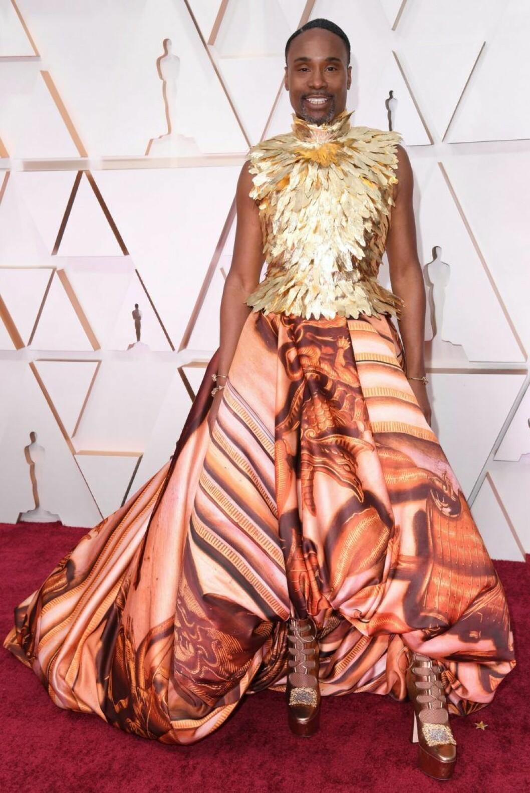 Billy Porter i guldig topp och kjol med mönster på röda mattan