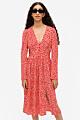 röd och vit mönstrad V-ringad klänning med knappar och långa ärmar