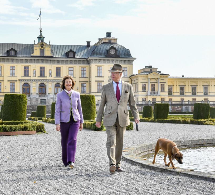 Kungen, drottningen och hunden Brandie framför Drottningholms slott