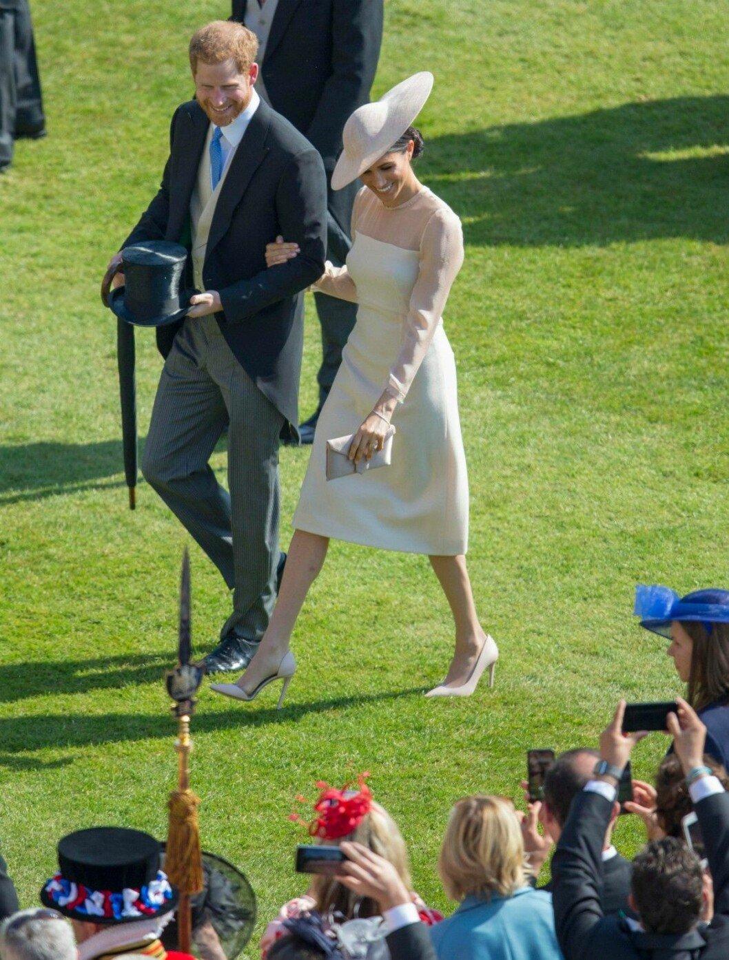 Meghan och prins Harry blir fotograferade av andra gäster under gardenpartyt på Buckingham Palace.