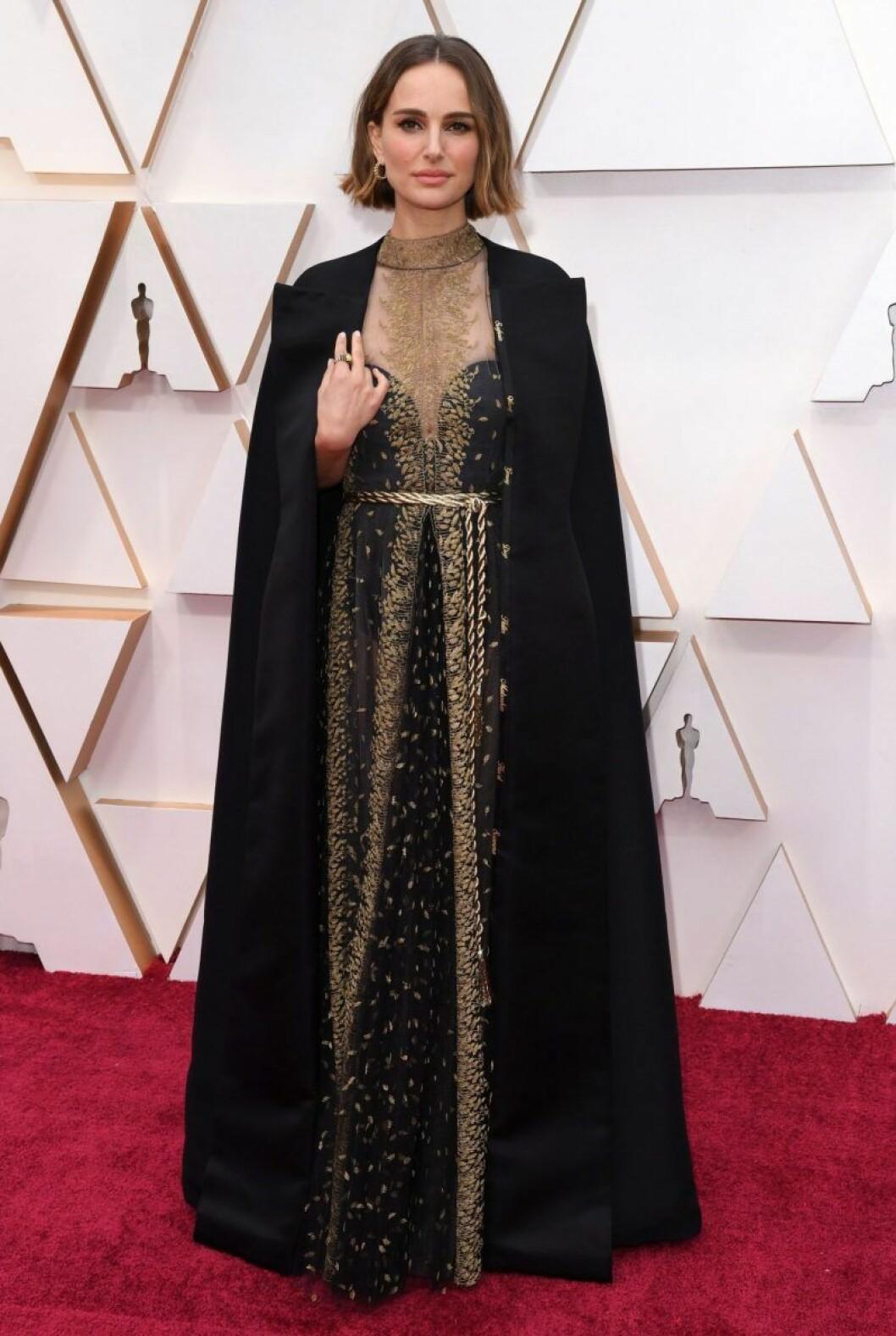 Natalie Portman i svart klänning med svart cape på röda mattan