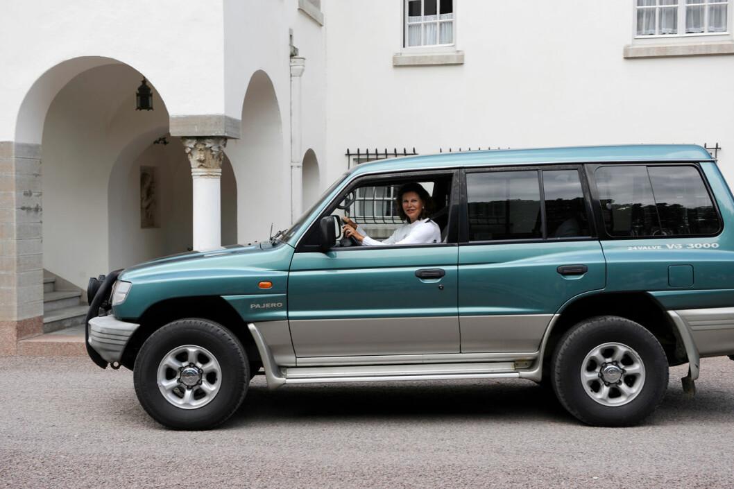 Drottning Silvia framför ratten på en stor bil utanför Solliden.
