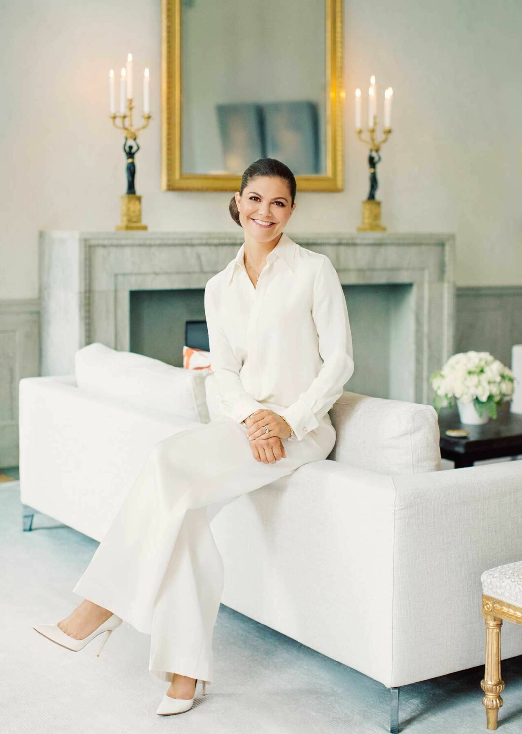 Kronprinsessan Victoria sitter på sin vita soffa hemma på Haga slott.
