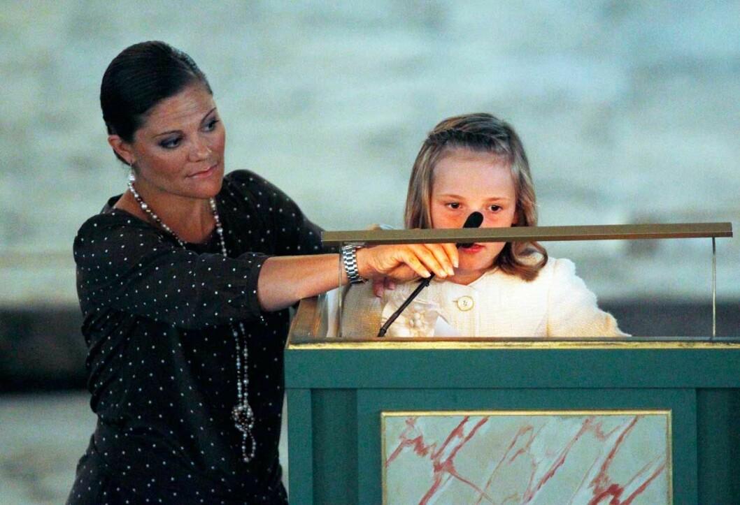 Kronprinsessan Victoria stöttar prinsessan Ingrid Alexandra som ska läsa ur bibeln i kyrkan, sju år gammal.